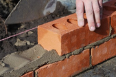 person laying bricks and mortar