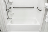 white fiberglass tub and shower with safety handles