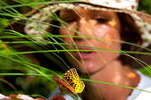 Woman watching butterfly in her garden.