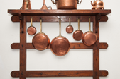 copper pots and pans on a rack