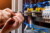 hands working on a circuit breaker