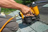 Carpenter uses nail gun on a roofing job.