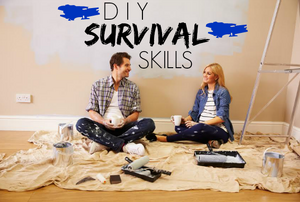 """A couple taking a break from painting a room with the words """"DIY Survival Skills."""""""