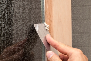 A putty knife is used to scrape excess putty from a window.