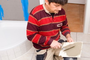 Applying mortar to ceramic tile with a trowel.