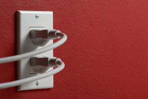 Two cords are plugged into an electrical outlet on a red wall.