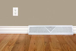 A baseboard heater on a wood floor.
