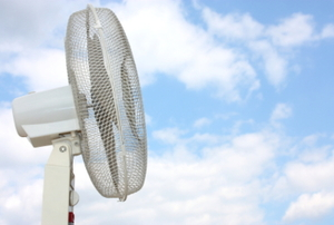 A standing fan against a partly cloudy blue sky.