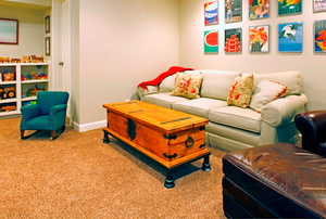 Carpet in a basement with a couch.
