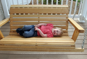 A smiling female toddler laying sideways on a wooden porch swing.