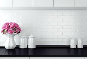 A black kitchen counter with a white backsplash and accessories.
