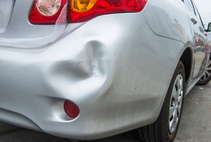 dent on the back of a white/silver car