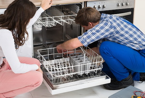 two people looking into a dishwasher