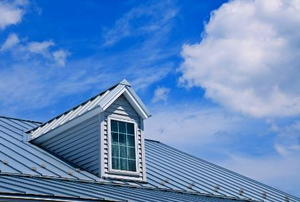 A window jutting out of a metal roof against a partly-cloudy sky.