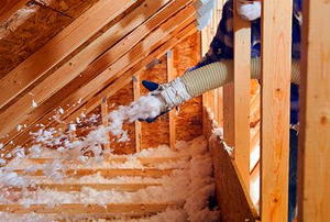 A worker spraying blown fiberglass insulation between attic trusses.