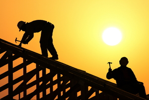 silhouette of two men on a roof with hammers