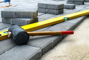 rubber mallet and level laying on paver stones
