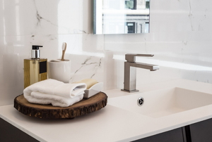A sleek modern bathroom with a hand towel and soap on a vanity.