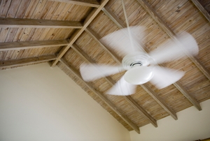a wooden ceiling peak with white ceiling fan in motion