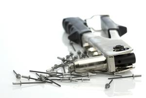 A pile of pop rivets next to a pop rivet gun.