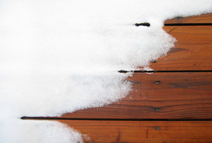 Snow on a wood deck.
