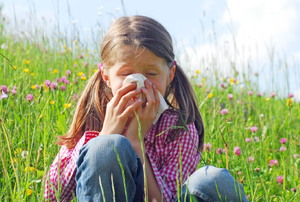 A little girl sitting in a grassy field and blowing her nose because she has a grass allergy.