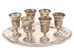 a silver tray holding six silver cups