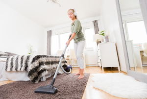 A woman uses a vacuum.