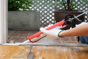 Using a caulking gun, sealant is used to finish a metal threshold.