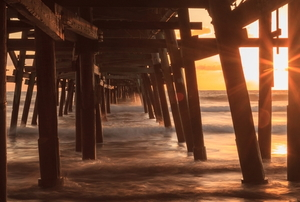 sun setting on an ocean under a wooden pier