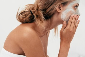 a woman applying a facial scrub