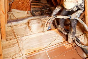 A worker installing white, foam insulation through a hose.