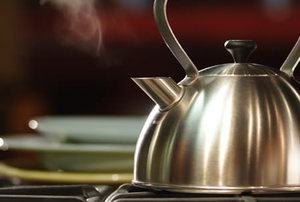 A steaming, stainless steel tea kettle.