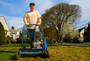 A man pushing a lawnmower toward the camera.