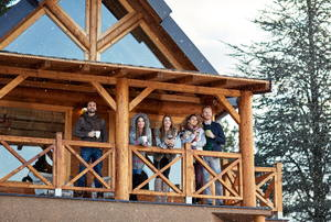 A group of adults standing on a balcony of a cabin in a winter setting.