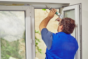 person applying caulk to the inside of a window frame