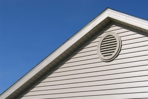 An oval soffit vent on the side of a roof.
