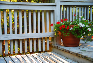 porch with a railing and potted flowers