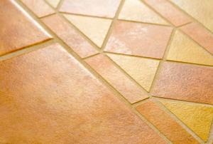 A floor covered in orange-yellow ceramic tiles