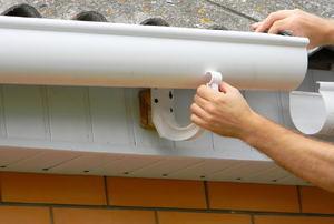 A woman installs gutters.