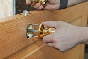 A pair of hands installing a doorknob on a door.
