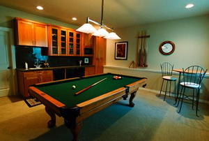 A room with a pool table and wine bar.