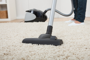 Person vacuuming an area rug