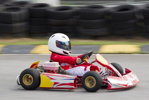 A kid drives a go kart.
