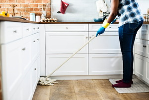 A woman cleans a kitchen.