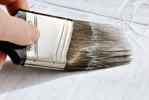 A paint brush applying primer.