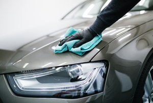 a silver car being polished with a blue cloth