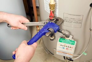 Plumber Pipe and Adjustable Wrenches on Water Heater Gas Line