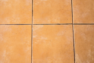 A beige tile floor with old, stained grout.