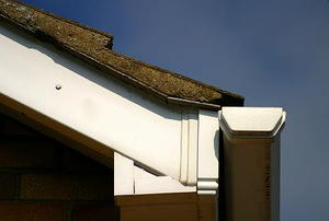 The corner of a roof, with soffit and gutter in plain view.